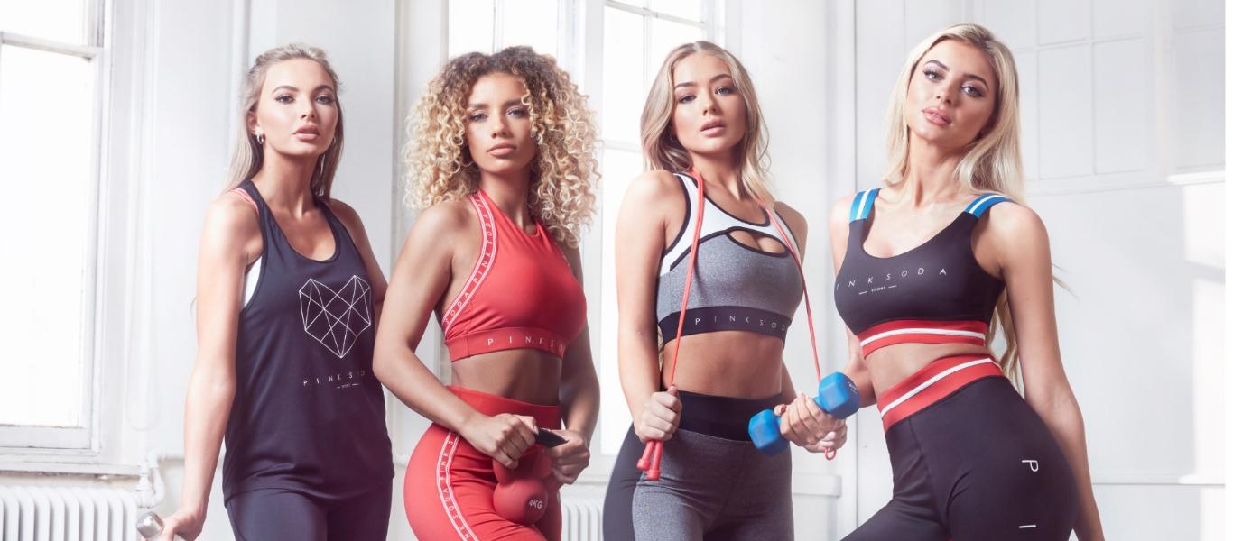 Vier Frauen im Fitnessstudio. alle tragen verschiedene Pink Soda Sport Fitness Outfits.